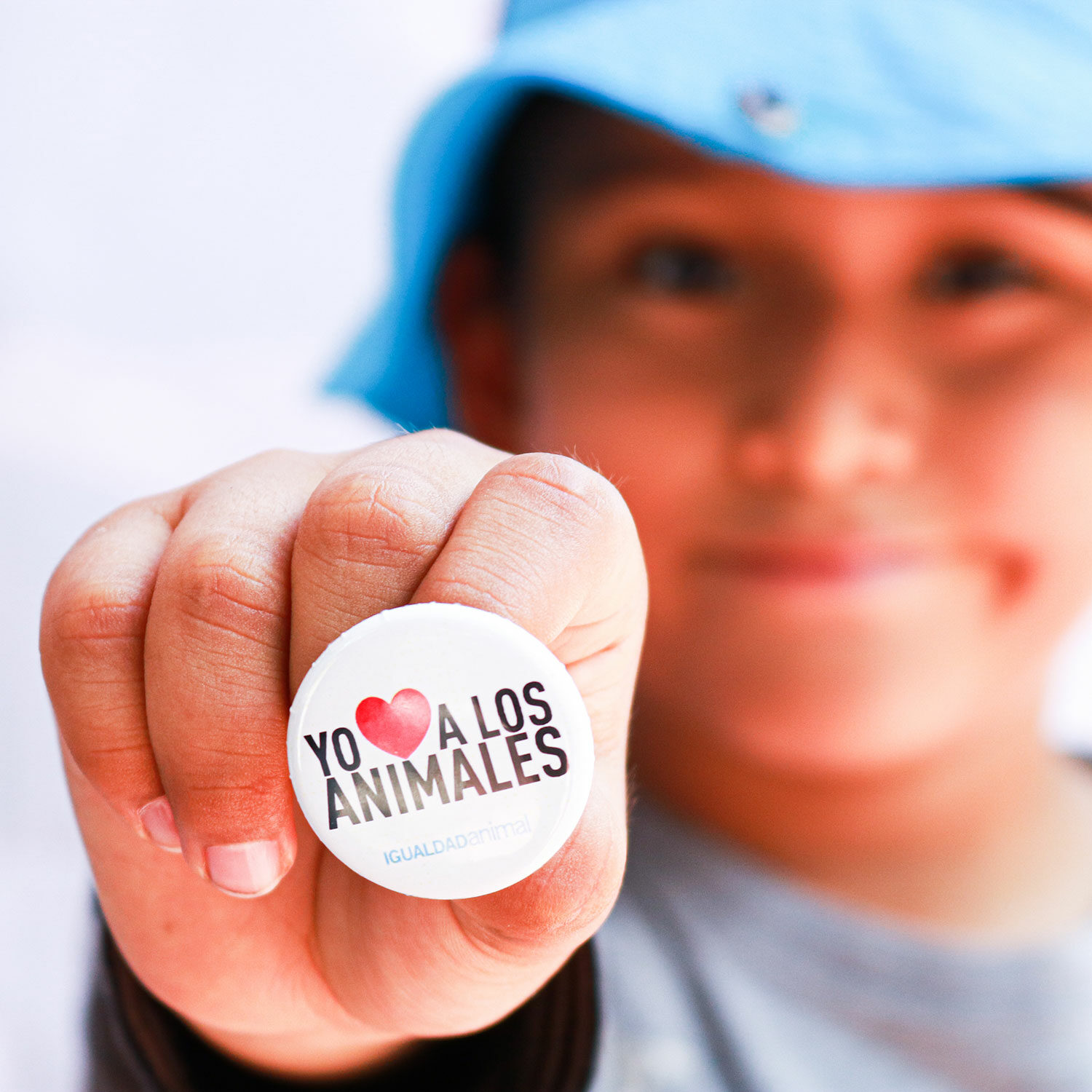 """Boy holding a pin that says """"I love all animals"""" in Spanish"""
